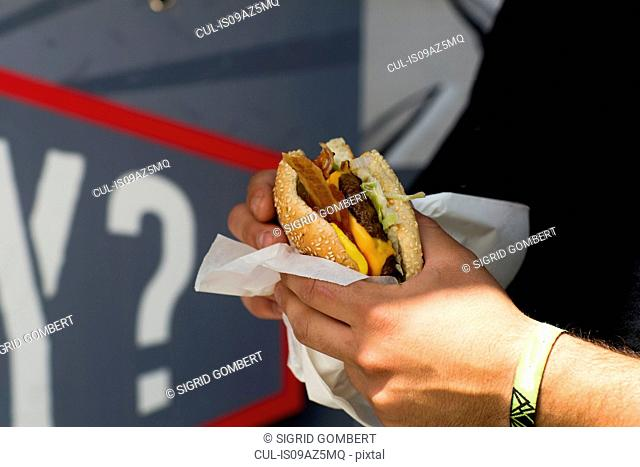 Male customer's hand eating hamburger from fast food van