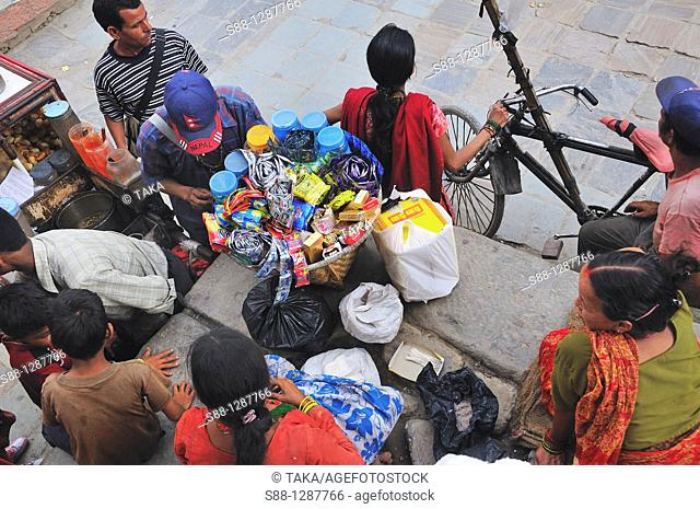 Many people selling little things on the corner of the street