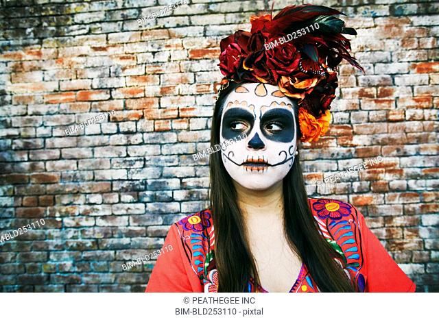 Hispanic woman near brick wall wearing skull face paint
