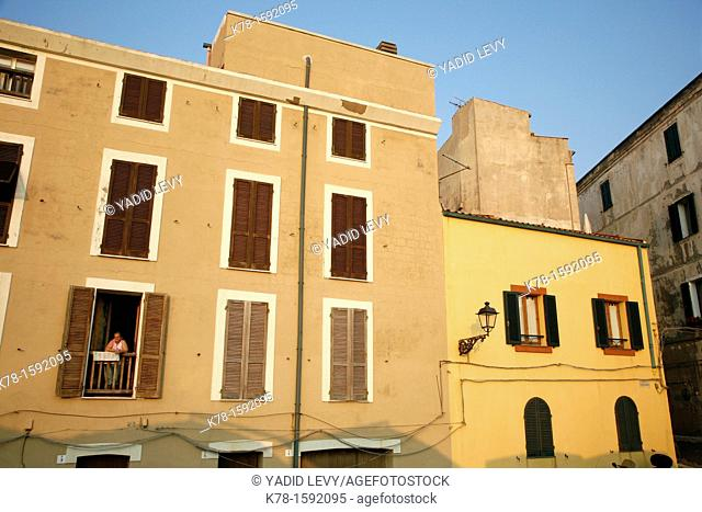 Woman standing in her window at a house built along the city walls  Alghero, Sardinia, Italy