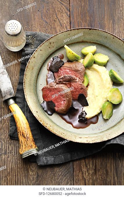 Saddle of venison with a Port and truffle sauce and mashed apples and potatoes