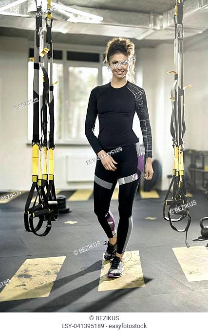Smiling girl is posing between hanging TRX straps in the gym on the windows background. She wears a dark sportswear with sneakers