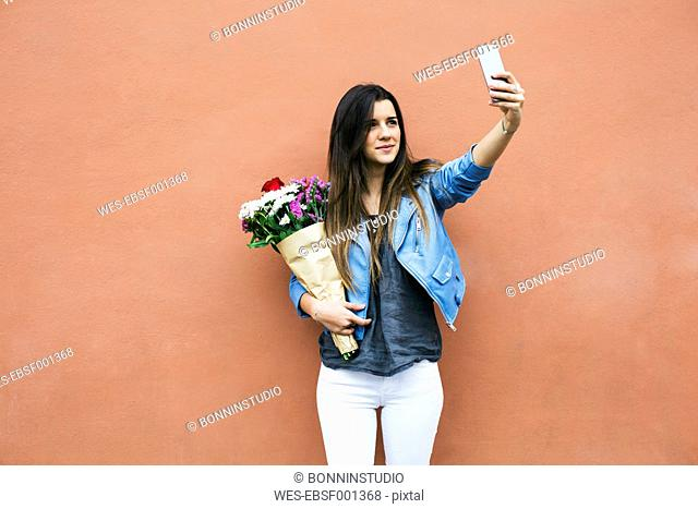 Young woman holding bunch of flowers taking a selfie