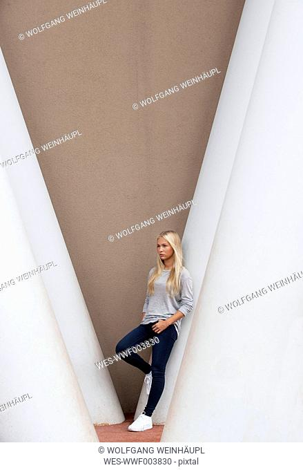 Portrait of blond female teenager leaning on concrete column
