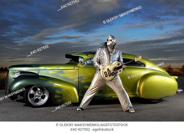Silver Elvis with a guitar standing in front of a custom lowride Studebaker hot rod under dramatic sunset sky  Performing artist Peter Jarvis from Toronto...