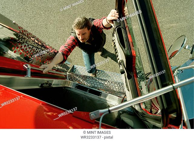A view looking down of a truck driver climbing into the cab of a commercial truck