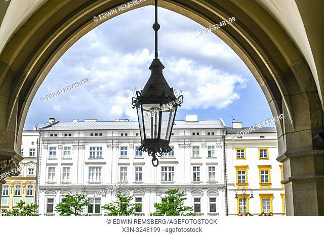 Street light hangs in archway of Krak—w Cloth Hall with historic townhouses behind it in Main Market Square of Krak—w Old Town, Lesser Poland Voivodeship
