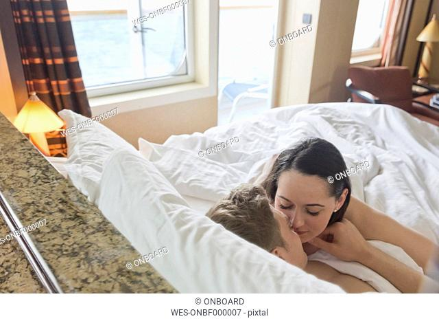 Young couple on cruise cuddling in bed