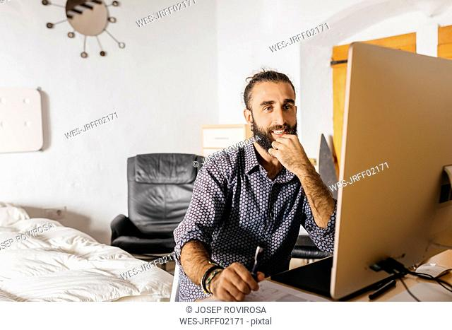Smiling young man working at home using the computer