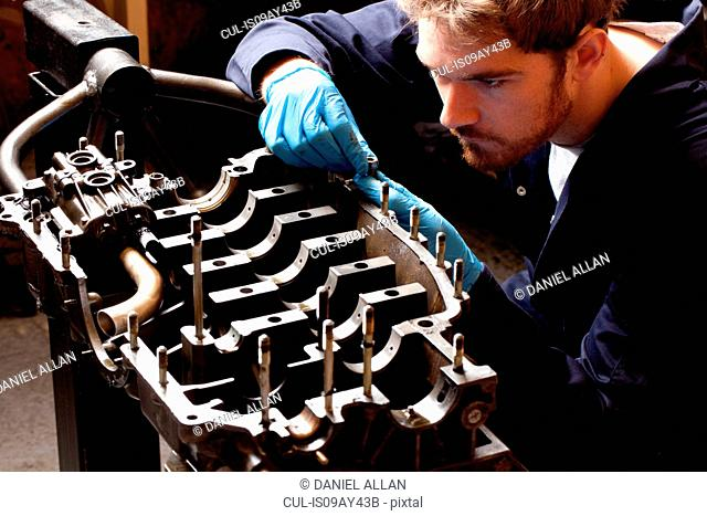 Male mechanic analysing car engine, stripped from car