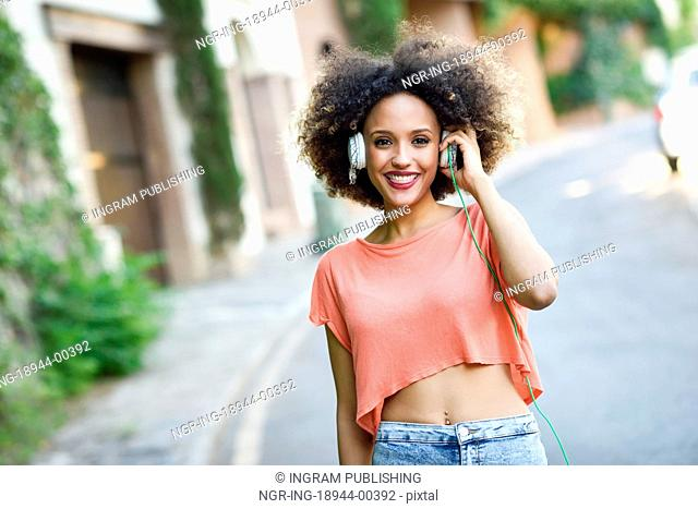 Portrait of young attractive black girl in urban background listening to the music with headphones. Woman wearing orange t-shirt and blue jeans with afro...