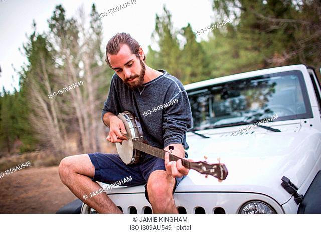 Young man playing banjo on jeep hood, Lake Tahoe, Nevada, USA