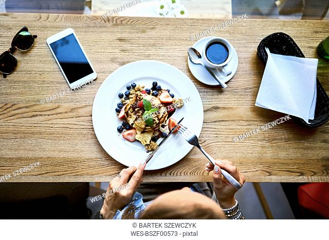 Overhead view of woman eating pancakes in cafe