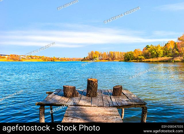 Stumps on old wooden fishing pier at sunny autumn day on river