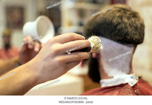 Barber shaving customer