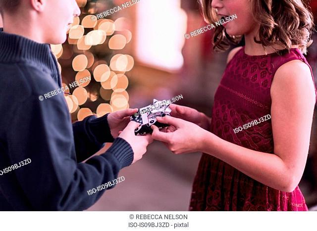 Boy handing over Christmas gift to girl