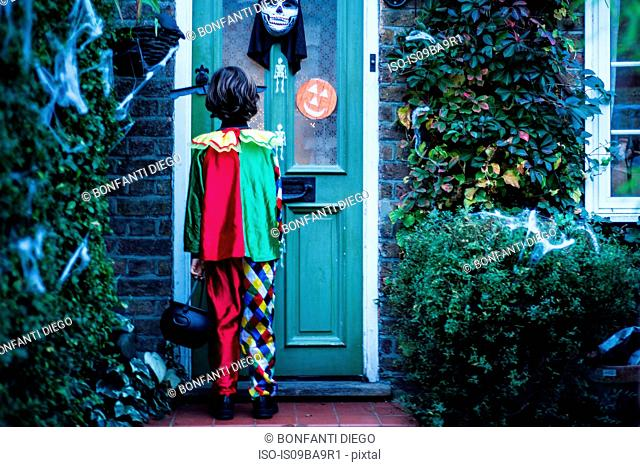 Young boy in halloween costume, standing at door, trick or treating, rear view