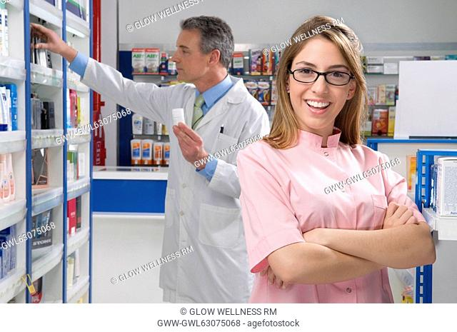 Female pharmacist smiling with a male pharmacist in the background
