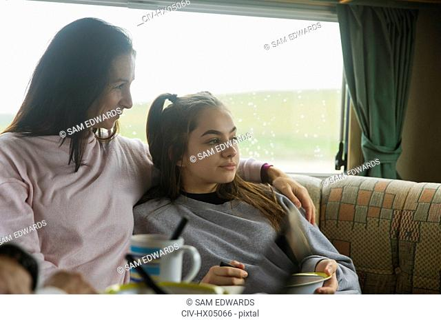 Affectionate mother and daughter enjoying breakfast in motor home