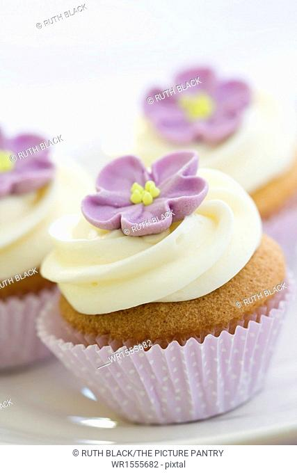 Mini cupcakes decorated with a purple sugar flower