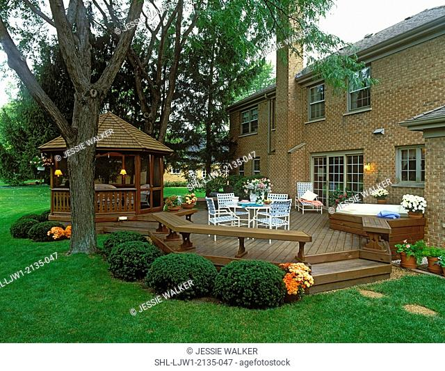 DECKS: Behind red brick house. Stained wood, hot tub, gazebo, table and chairs, shrubs and mums around foundation. View from two different angles