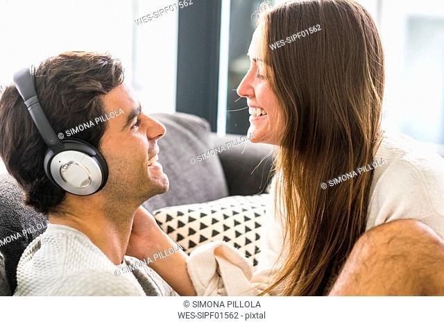 Smiling young woman looking at man wearing headphones at home