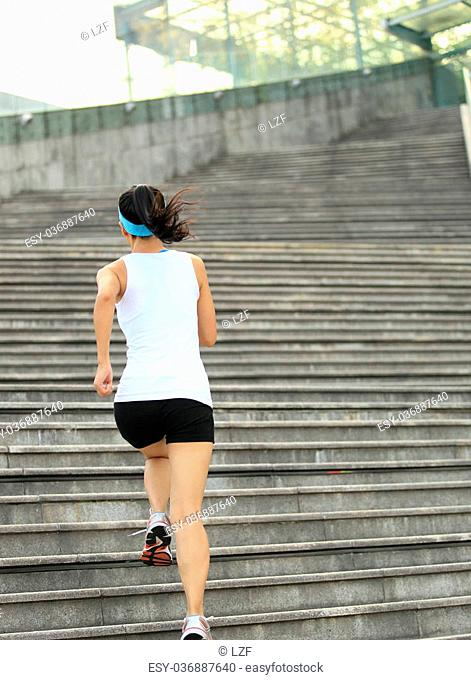 Runner athlete running on stairs. listening to music in headphones from smart phone mp3 player woman fitness jogging workout wellness concept