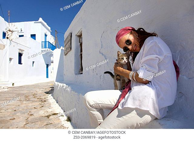 Woman with a local cat, Amorgos, Cyclades Islands, Greek Islands, Greece, Europe