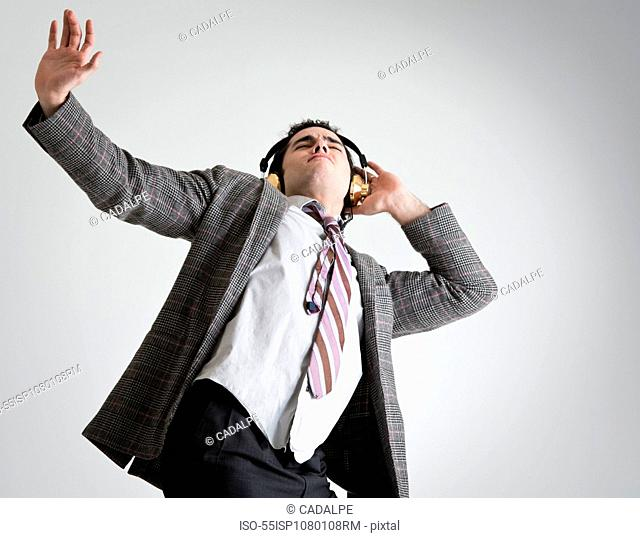 Businessman wearing headphones dancing