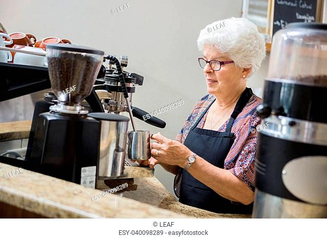 Senior waitress steaming milk for coffee in cafe