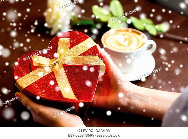 holidays, valentines day, love and people concept - close up of hands holding heart shaped gift box over snow