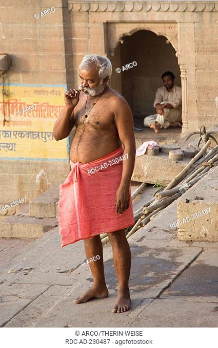 Indian man brushing his teeth, at a Ghat, Varanasi, Benares, Uttar Pradesh, India