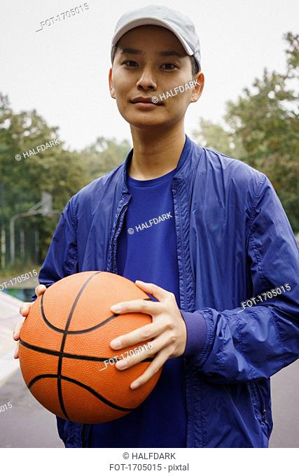 Portrait of young man holding ball while standing at park