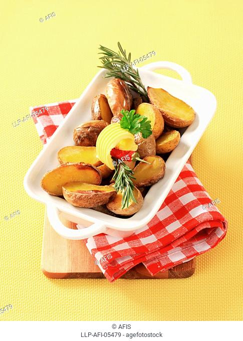 Halves of roasted potatoes and butter - detail