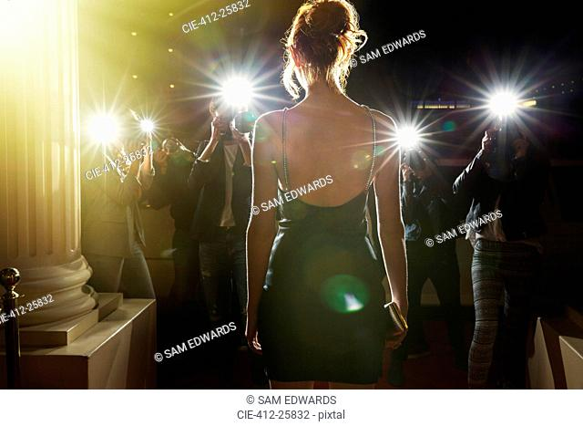 Silhouette of celebrity in black dress being photographed by paparazzi