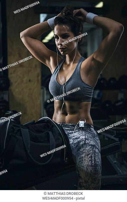 Female athlete sitting on bench in gym