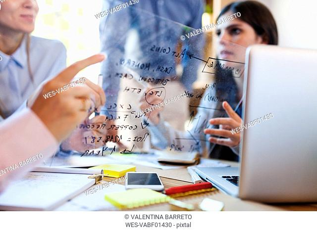 Business team discussing formula on glass pane in office