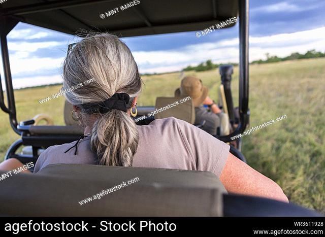 A woman with grey hair seated in a safari vehicle, obserrving wildlife