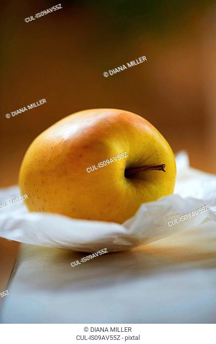 Yellow apple on greaseproof paper