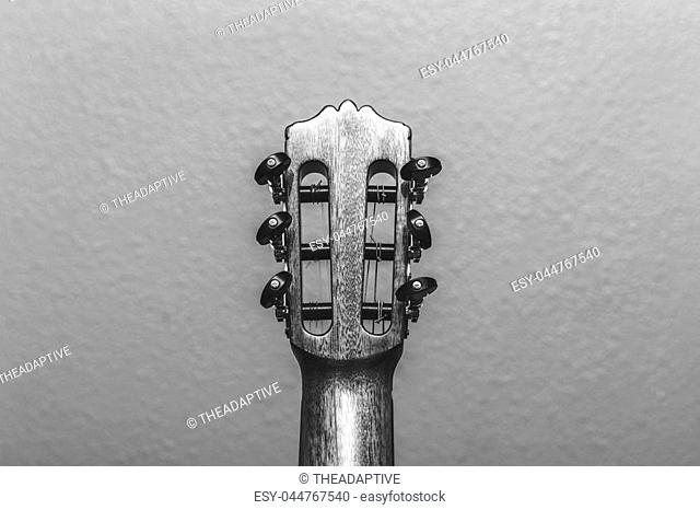 Headstock of an acoustic guitar seen from the back side photographed in black and white