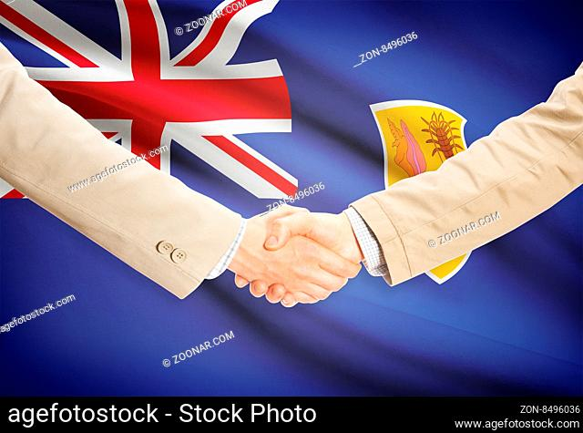 Businessmen shaking hands with flag on background - Turks and Caicos Islands