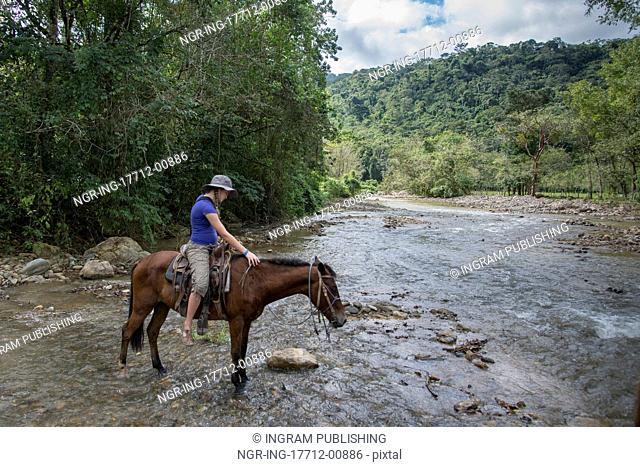 Teenage girl crossing a river on a horse, Finca El Cisne, Honduras