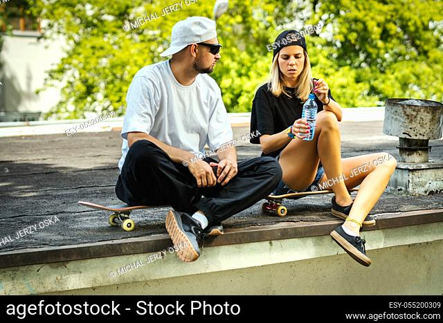 skateboard boy and girl sitting and drinking water on a summer day