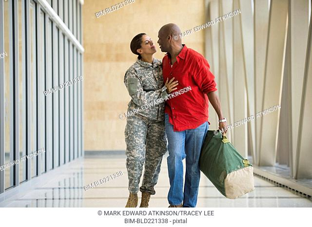 African American soldier talking to husband in airport