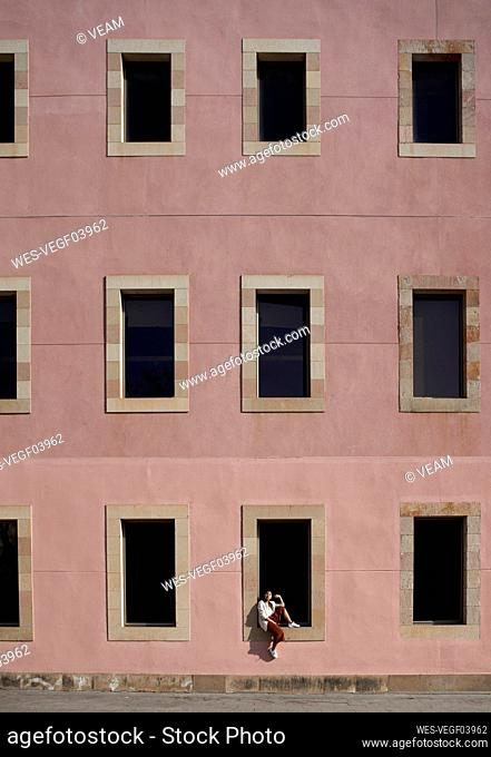 Woman sitting on window sill of building