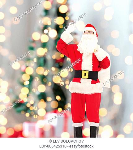 christmas, holidays, gesture and people concept - man in costume of santa claus with bag waving hand over tree lights background