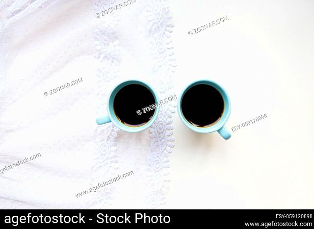 two cups of coffee with croissants on the background of laces on a white background, close-up