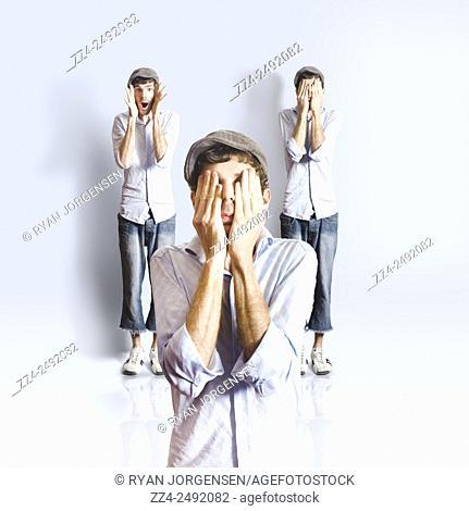 Silly men in full length playing peek a boo in a blue studio portrait. Big kid
