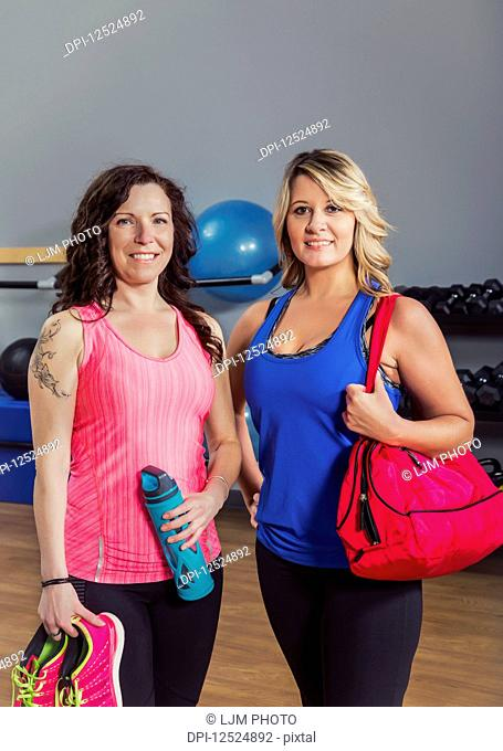 Two attractive middle-aged women posing for the camera after working out at a fitness class in a gym; Spruce Grove, Alberta, Canada