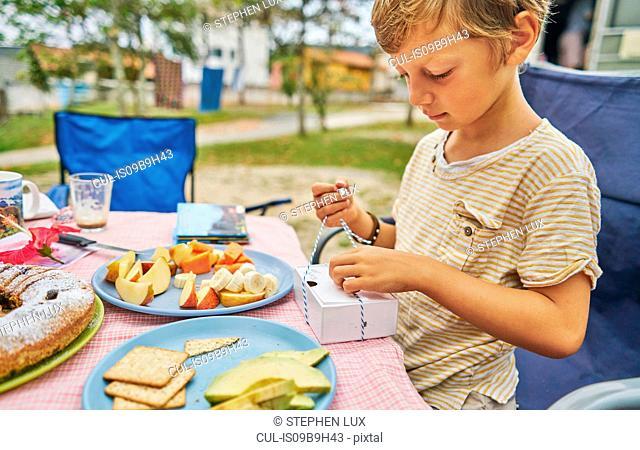 Boy at picnic table opening present, Florianopolis, Santa Catarina, Brazil, South America
